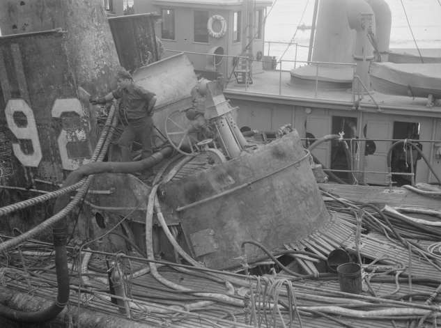 In the aftermath of the USS Squalus submarine rescue, a Portsmouth Naval Shipyard worker inspects damage to the sub.