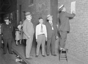 Boston Police in 1930 in Chinatown post a sign in Chinese warning against starting a Tong War. (Boston Public Library Leslie Jones Collection).