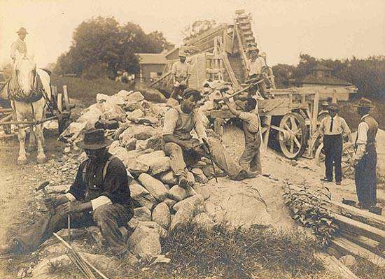 Workers reducing stonewalls to roadbeds