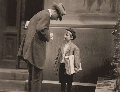 Lewis Hine with Michael McNelis, 8-year-old newsboy. Michael had just recovered from his second attack of pneumonia. He was found selling papers in a rainstorm. Philadelphia, Pa.