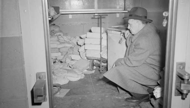 A detective examines the Brinks vault after the theft. Photo courtesy Boston Public Library, Leslie Jones Collection.