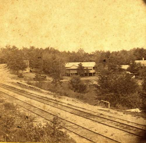The Fitchburg Railroad tracks, late 1860s, with amusement park buildings in the background.