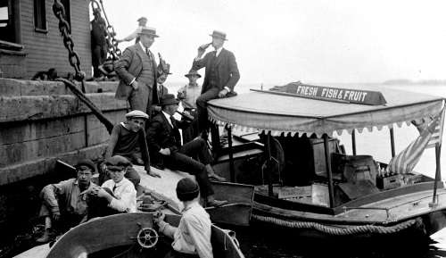 "Boat with sign ""Fresh Fish and Fruit"" delivers bottled drinks to men on pier (possibly Prohibition selling illegal alcohol). Photo courtesy Boston Public Library, Leslie Jones Collection."