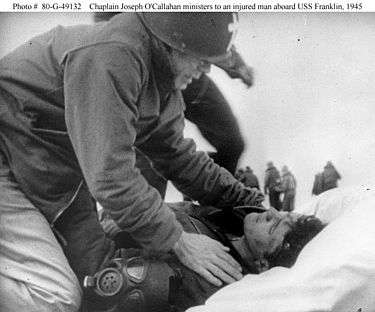 Father Callahan helping the wounded aboard the USS Franklin.