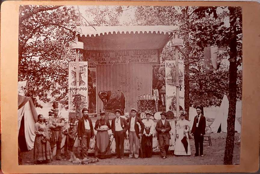 A Kickapoo Medicine Show company in front of a stage.
