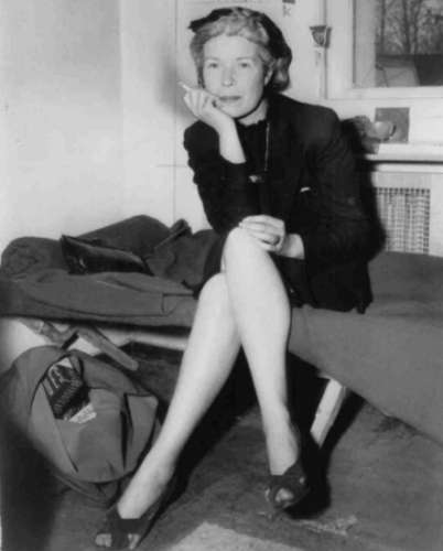 "Mildred Gillars, ""Axis Sally,"" seated on cot, smoking cigarette, in U.S. Counter Intelligence Headquarters, Berlin, Germany in 1946"