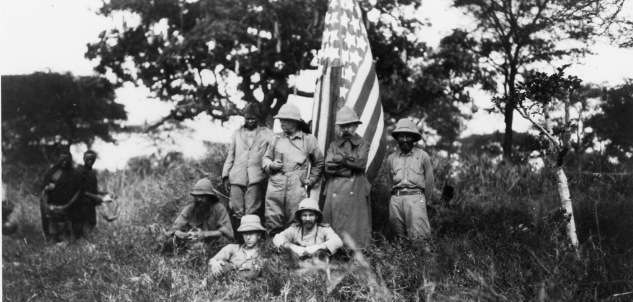 Roosevelt stands to the left of the flag.