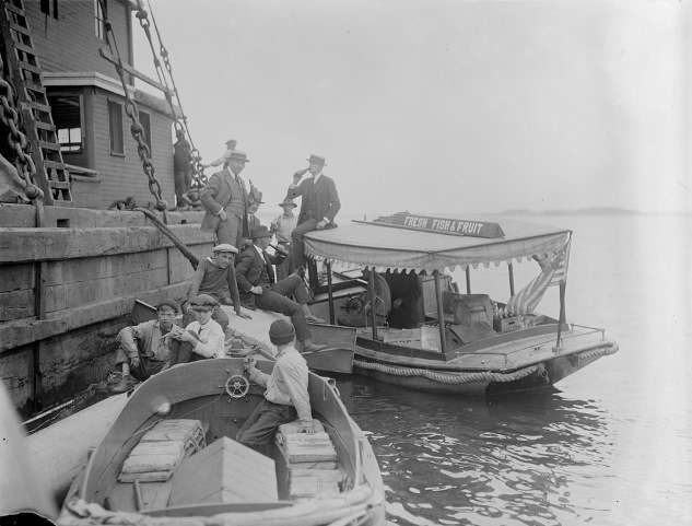 "Boat with sign ""Fresh Fish and Fruit"" delivers bottled drinks to men on a Boston Harbor pier (probably selling illegal alcohol). Photo courtesy Boston Public Library, Leslie Jones Collection."