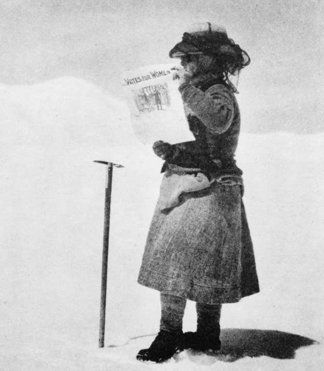 "Fanny Bullock Workman with newspaper that reads, ""Votes for Women."""