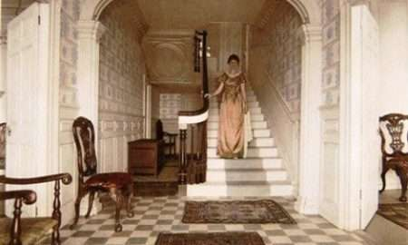 Colonial woman descending staircase.